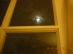 The Moon!  Looking white and ghostly through the French doors at the back of her house.