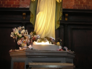 This Virgin Mary, of aof somewaht more modern visage tha the rest of the Church Figures.  Notice the piles of photograph at her feet.  Wonder what they're for?