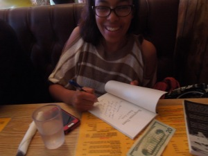 Raina J. Leon signing a copy of her book, Boogeyman Dawn, at Puerto Alegre on Valencia St.
