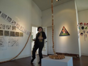 Artist Janet Self, standing next to her piece in the 2nd floor of Odd Fellows Hall's art gallery