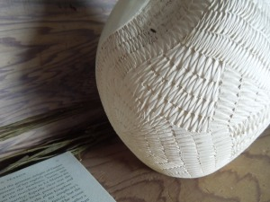 The etchings on the surface of the pot, and the open book = metaphors. For Depth. Right?