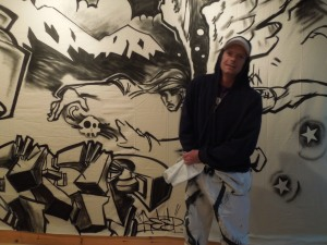 This is Bones, a graffiti artist. He's standing in front of his latest creation, in a gallery on Laurel Street in Fort Bragg.